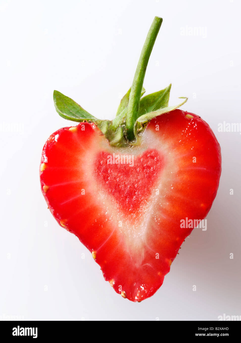 Heart shaped Organic strawberry slice , stylised creative concept photo representing a healthy heart, against a - Stock Image