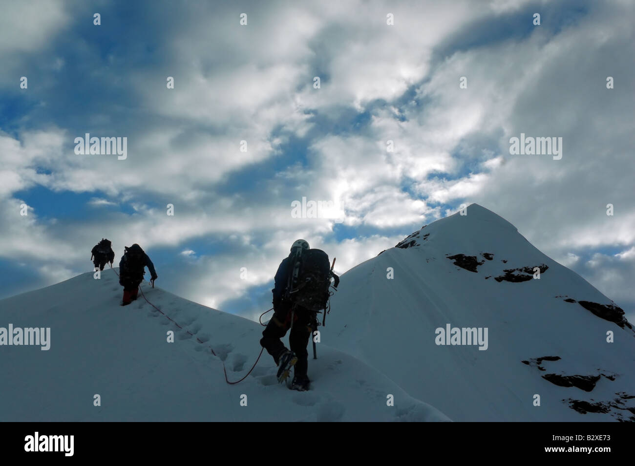 Climbers on the way to the second summit of Pequeno Alpamayo, part of Bolivia's Cordillera Real - Stock Image