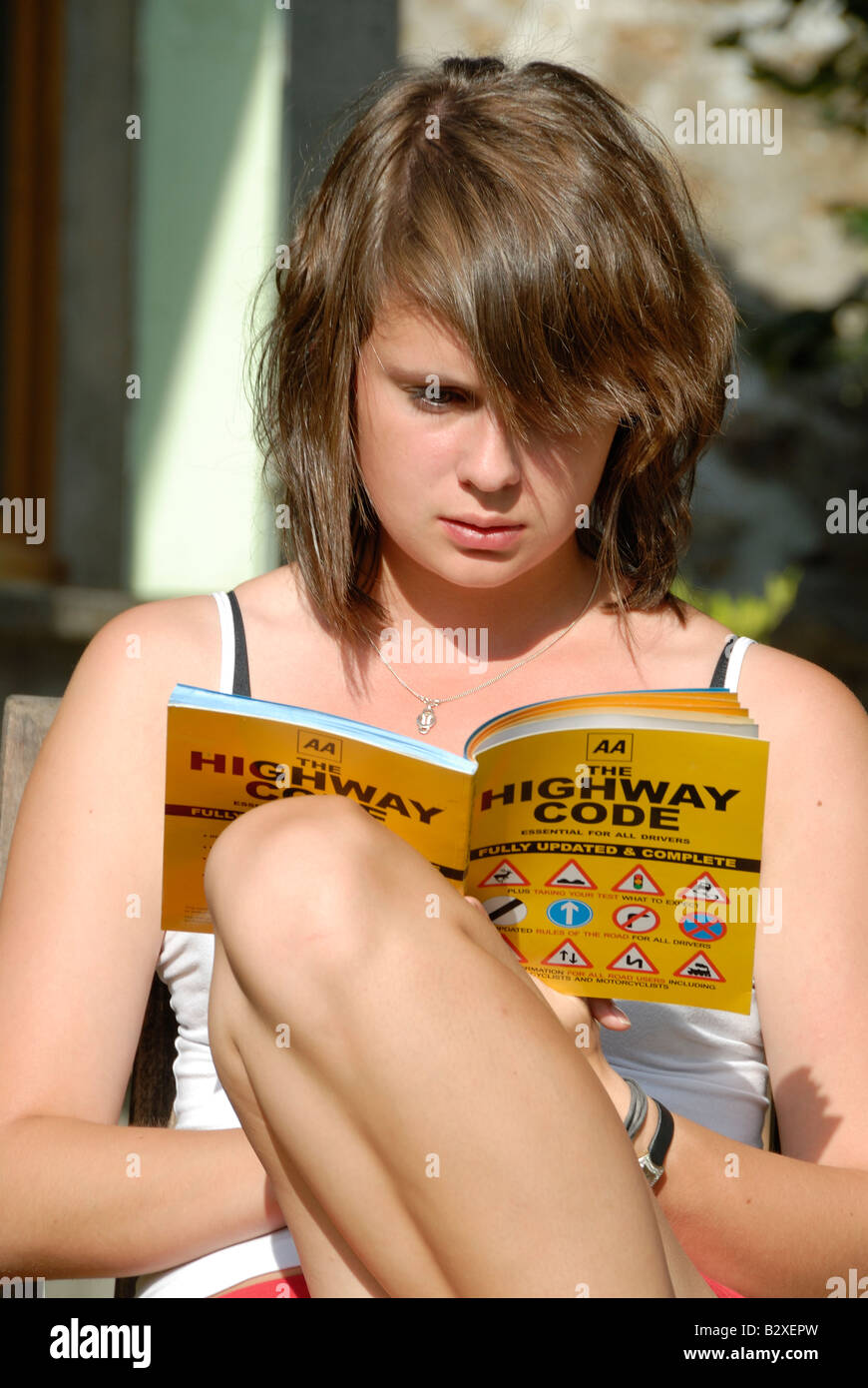 Stock photo of a teenage girl reading the highway code as she prepares for her driving theory test in the UK - Stock Image
