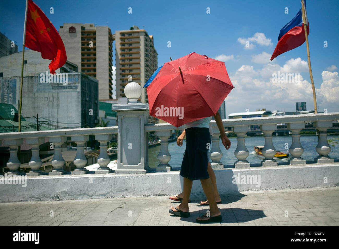 A couple shield themselves from the midday sun with umbrellas while crossing the Pasig River on a bridge in Manila, - Stock Image