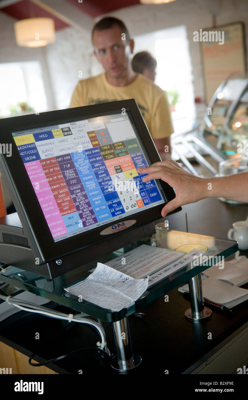 Cafe worker using a digital touch sensitive monitor screen computerised till to add up the bill in restaurant - Stock Image