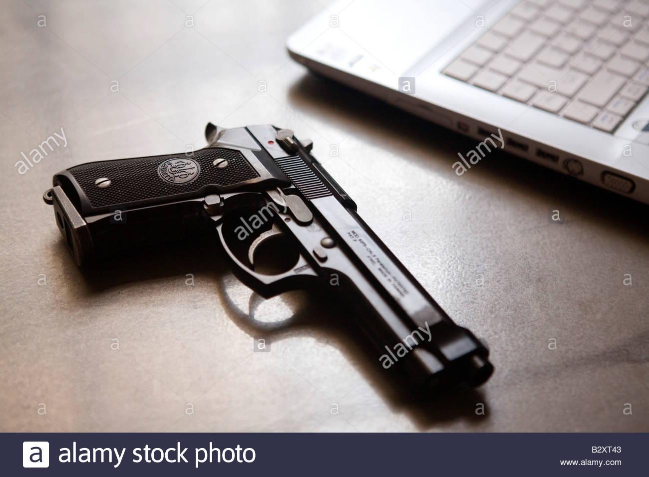 gun and laptop, office - Stock Image