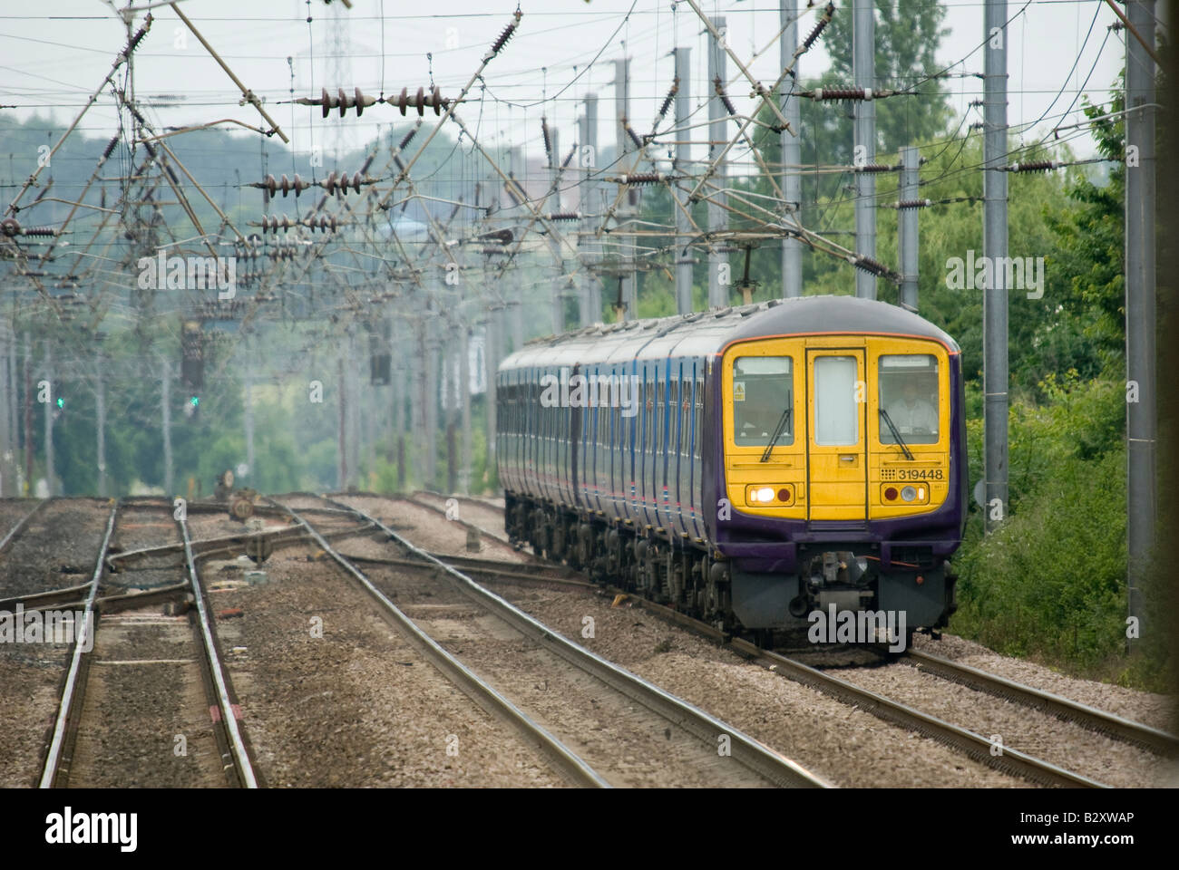 class 319 train in first capital connect livery travelling beneath catenary in the uk Stock Photo