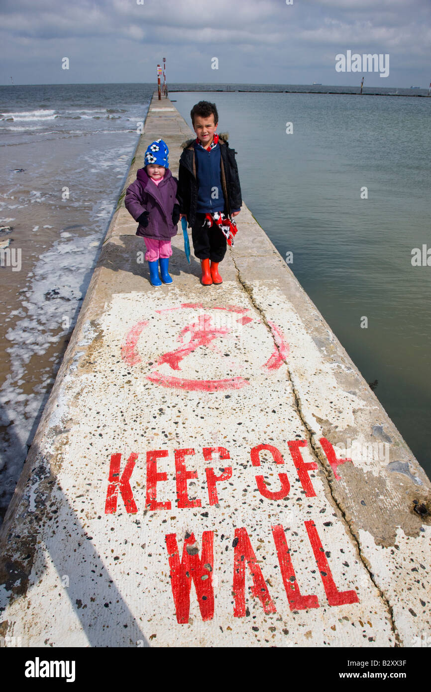 Children standing on a sea wall with a sign stating Keep Off Wall - Stock Image
