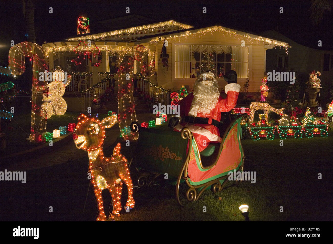 House With Christmas Lights.Santa Claus Waving In Front Of House With Christmas Lights