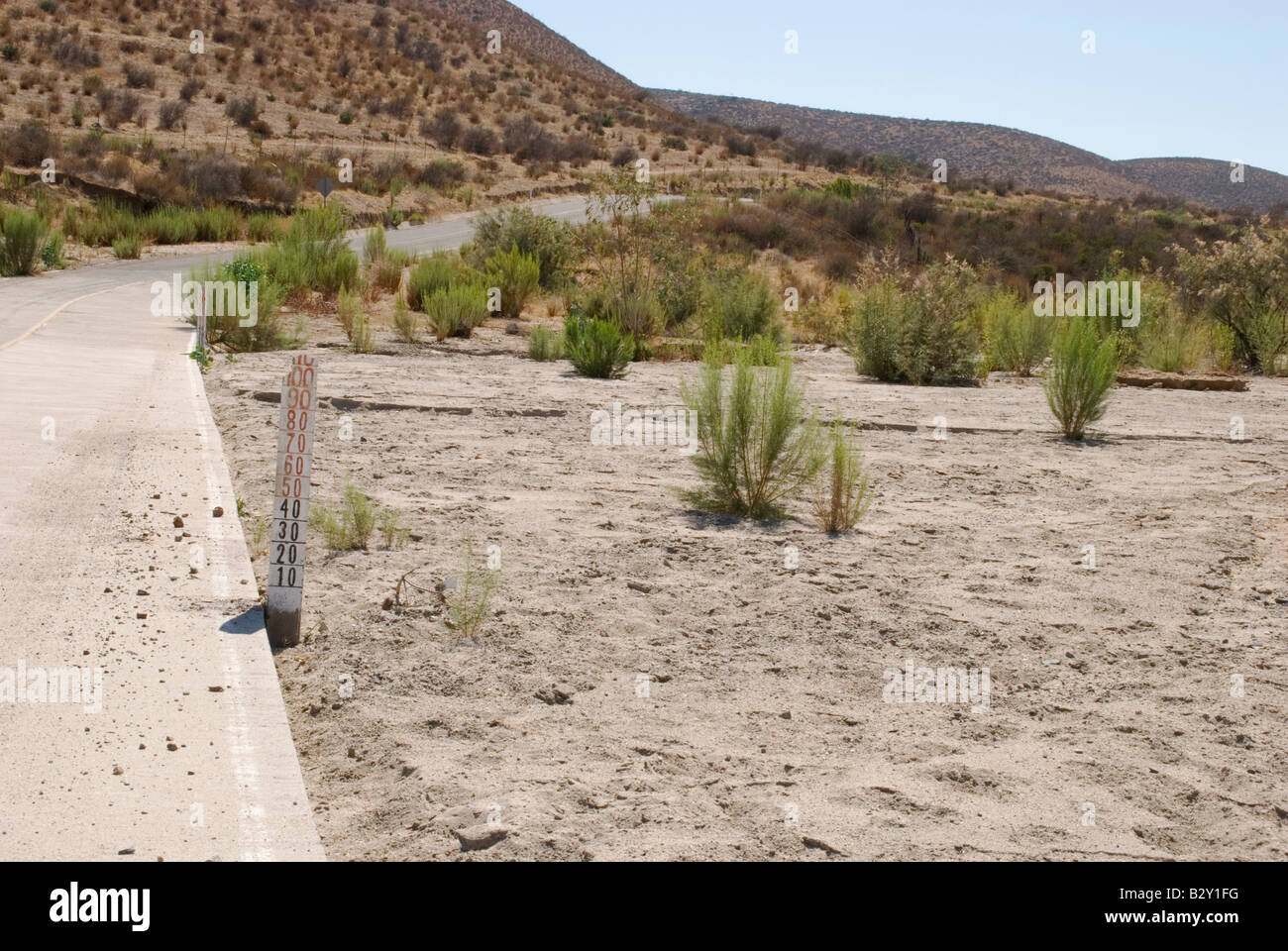 Water depth markers alongside a road subject to flash floods in Baja CA, Mexico - Stock Image