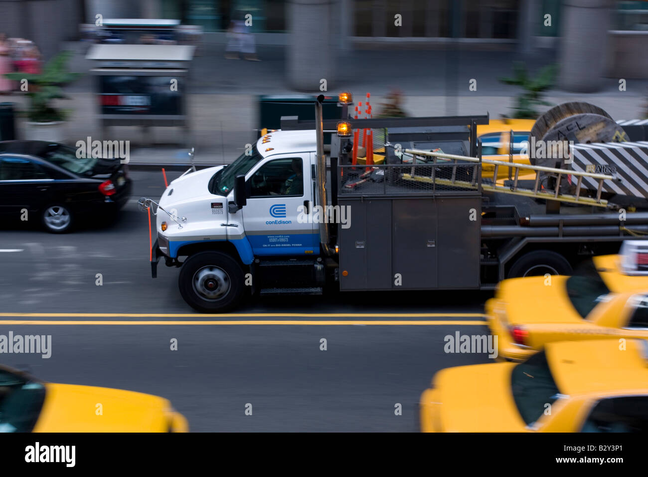 A Consolidated Edison heavy truck navigates through midtown traffic on the way to a work site. - Stock Image
