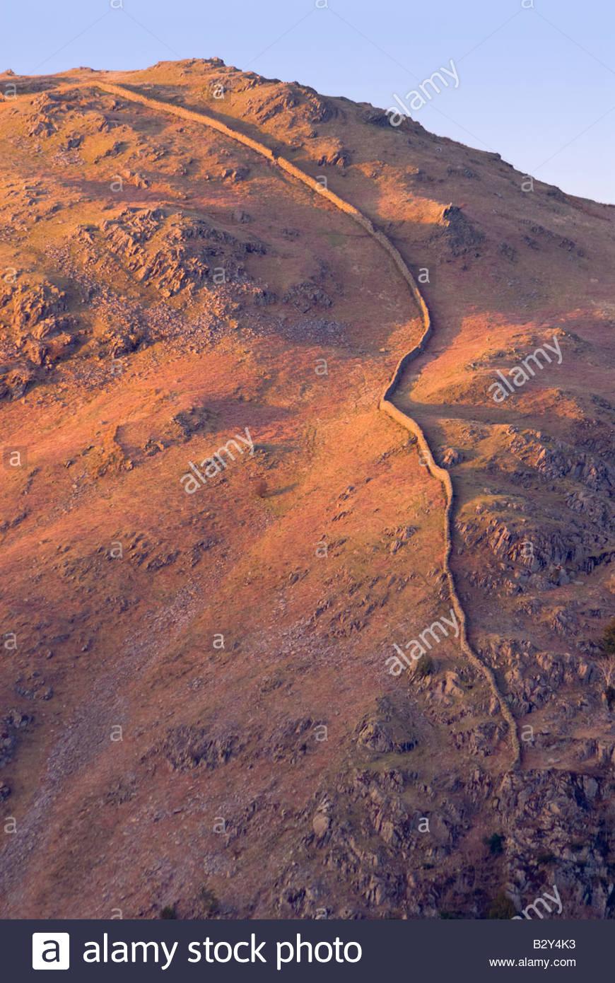 Stone wall on mountainside, Lake District, Cumbria, England. - Stock Image