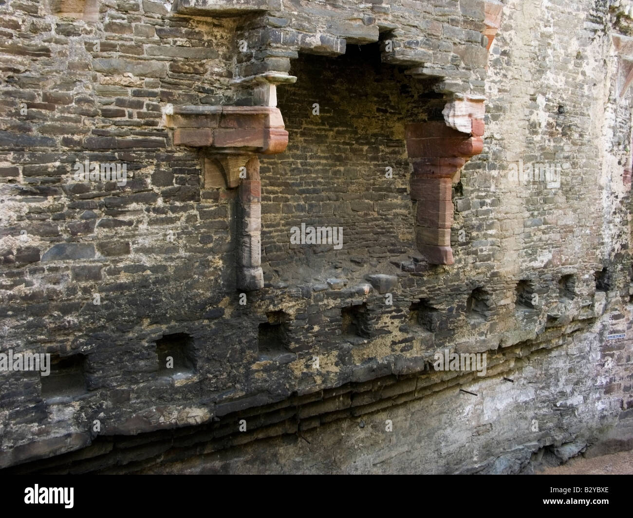 Fireplace and holes for the floor timbers in the Great Hall, Conwy Castle, Conwy, North Wales, UK - Stock Image