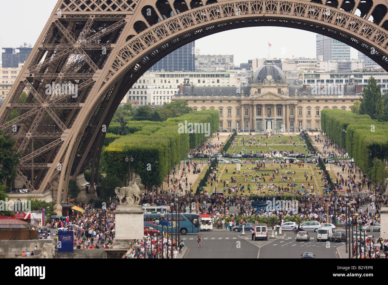 Groups of people in the shadow of the Eiffel Tower and Parc du Champ de Mars in the background Paris France - Stock Image