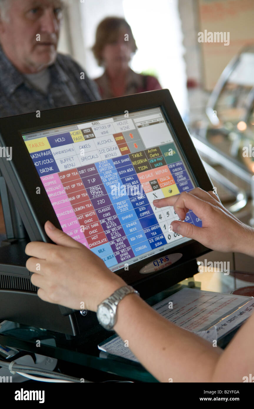 Cafe worker using a digital touch sensitive screen on computerised till to add up the bill - Stock Image