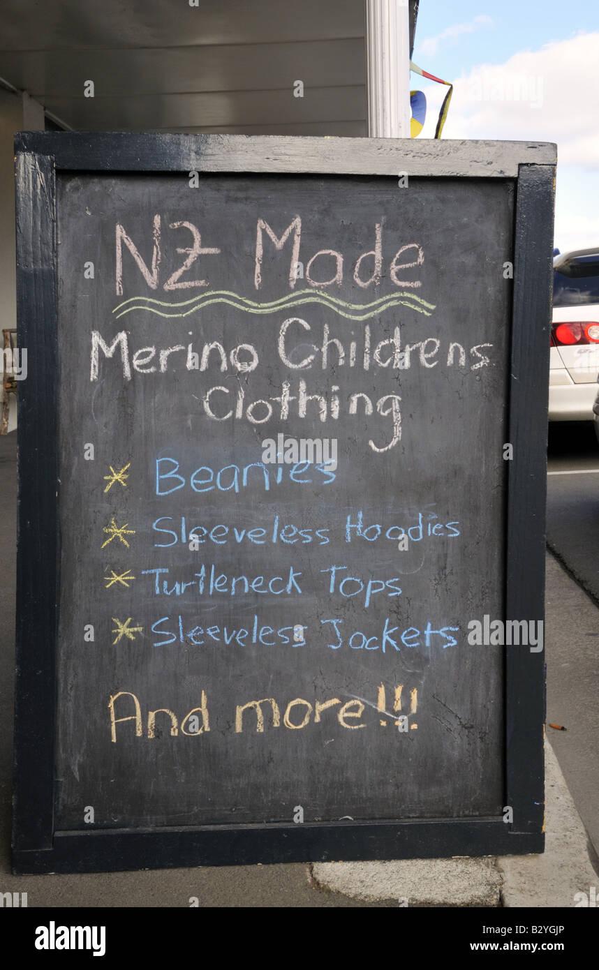 Handwritten chalkboard advertisement of New Zealand made merino children clothing - Stock Image