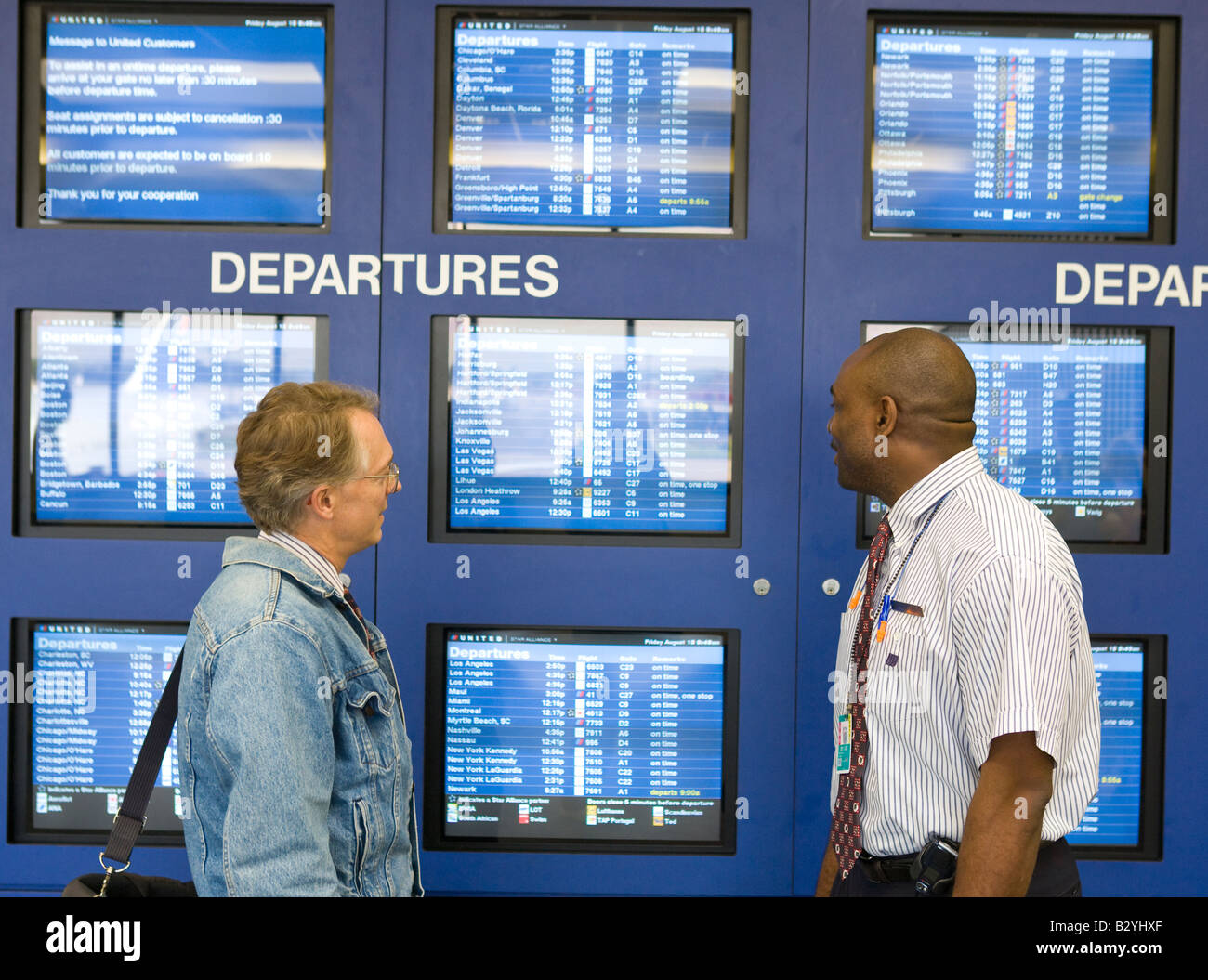 a united airlines worker talks to a passenger in front of the stock