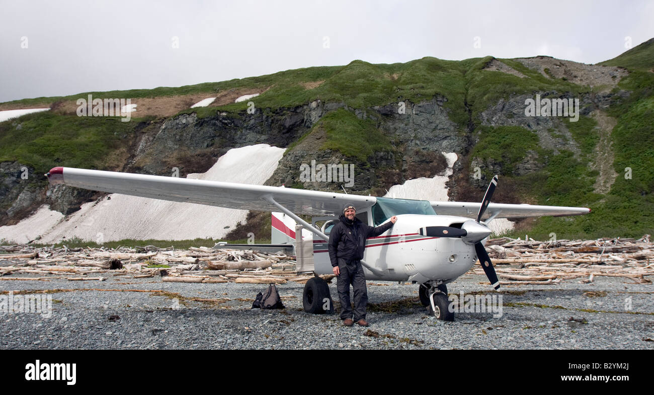 K-Bay Air air plane (Cessna 206) and pilot standing on a gravel beach of the Katmai National Park and Preserve, Stock Photo
