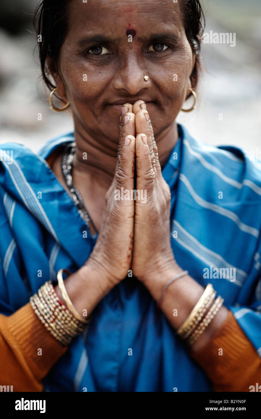 A Hindu, Indian woman wearing a colorful sari and decorative jewelry holds her hands up together in a prayer. - Stock Image
