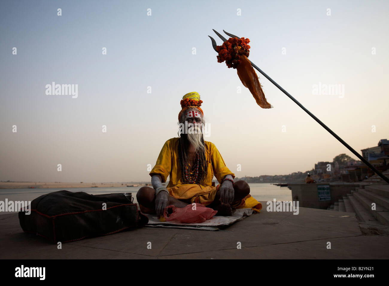 An Indian sadhu man sits in meditation posture near the bank of the Ganges river. - Stock Image