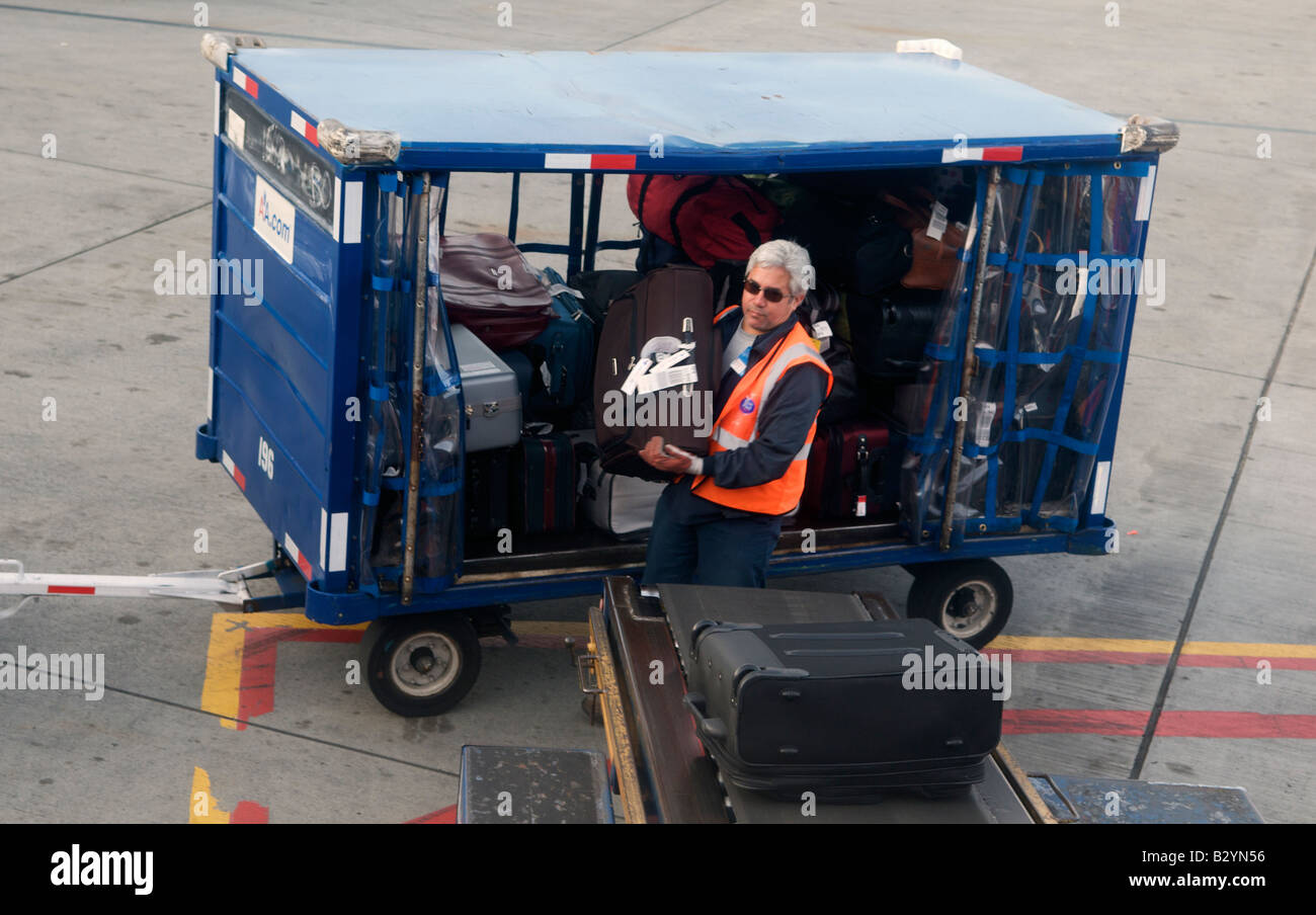 A baggage handler loads a suitcase on to a conveyer belt at Dallas Fort Worth International Airport in Texas, United - Stock Image