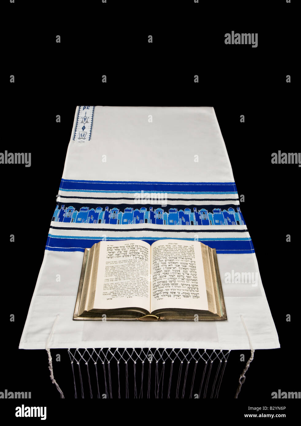 A Jewish prayer book, or Siddur, on a prayer shawl, or tallit, against a black background. - Stock Image
