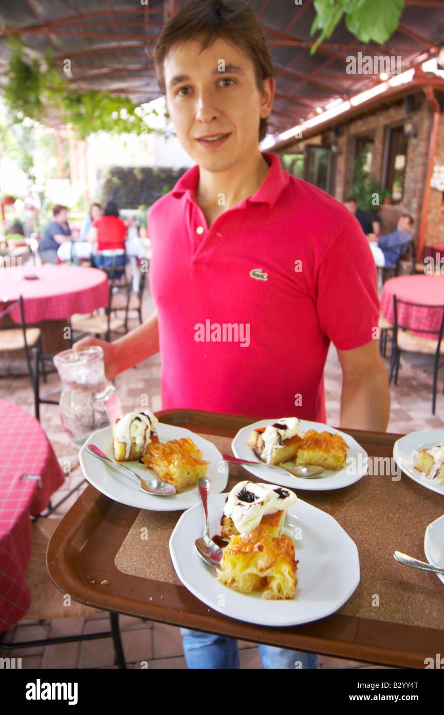 Waiter serving typical Greek dishes. Rakokazano restaurant in Strantza village near Naoussa. Macedonia, Greece. - Stock Image