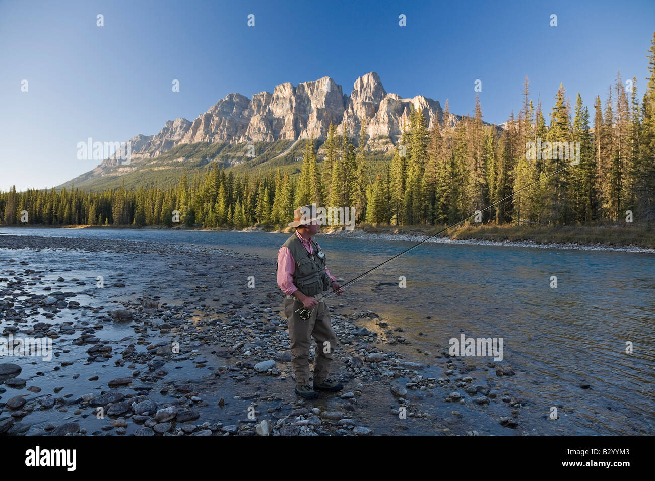 Man Fishing in Mountain River, Banff National Park, Alberta, Canada Stock Photo