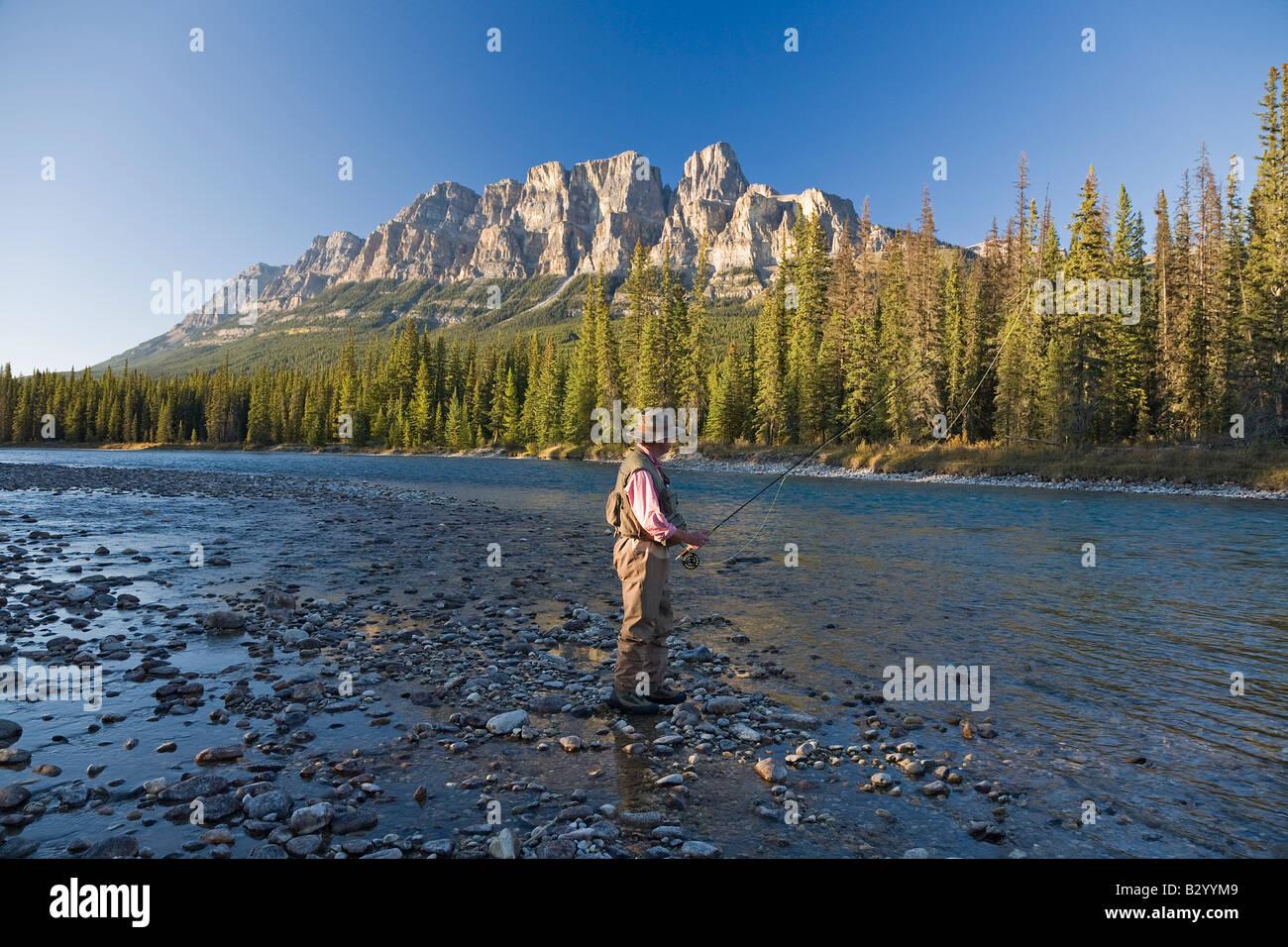 Man Fishing in Mountain River, Banff National Park, Alberta, Canada Stock Photo