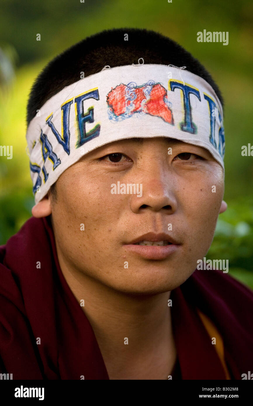 A monk wears a headband with a slogan that states 'Save Tibet'. - Stock Image