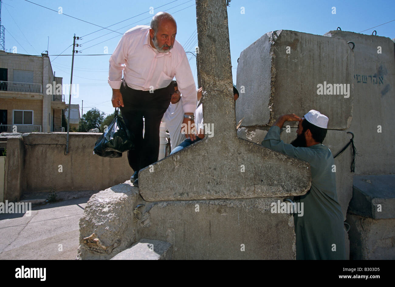 Men climbing to cross the Israeli West Bank barrier, West Bank, Palestine, Middle East - Stock Image