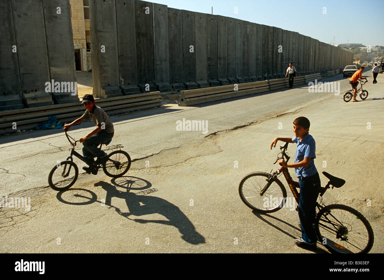 Boys playing on bicycles by the Israeli West Bank barrier, West Bank, Palestine, Middle East - Stock Image