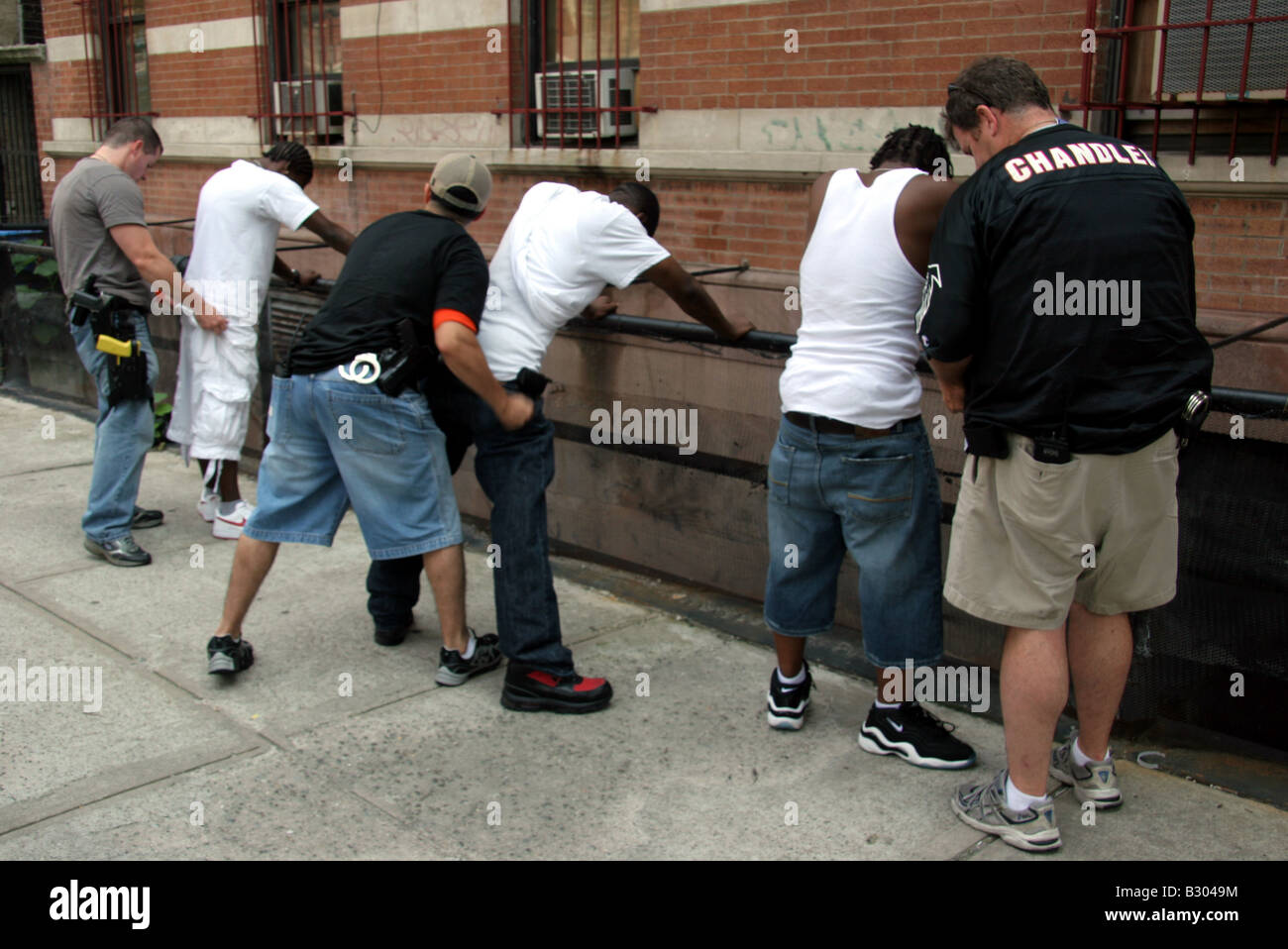Plain clothes police detectives searching suspects in Harlem New York City - Stock Image