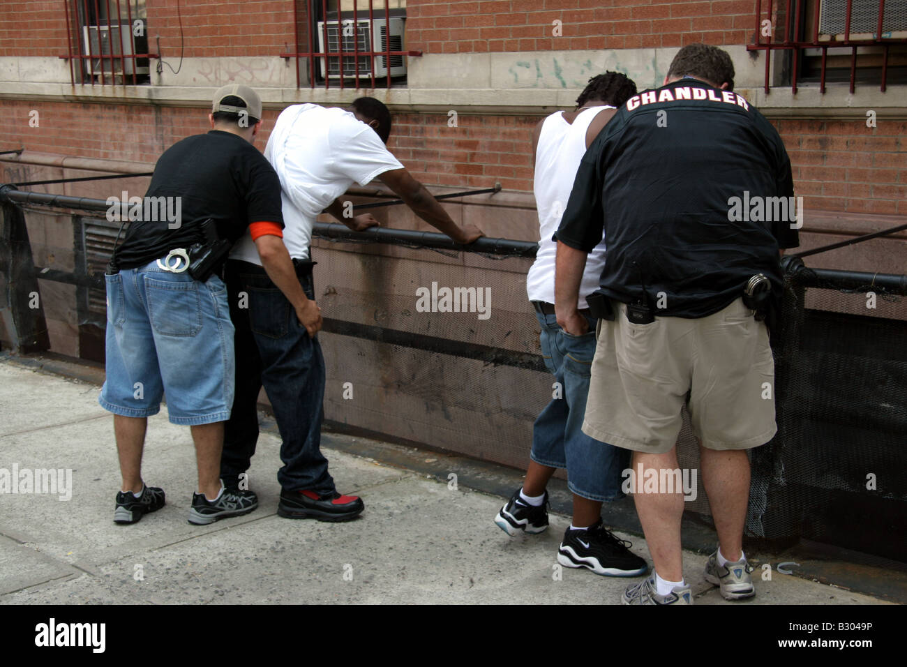 Plain clothes police detectives searching suspects on the street in Harlem New York City - Stock Image