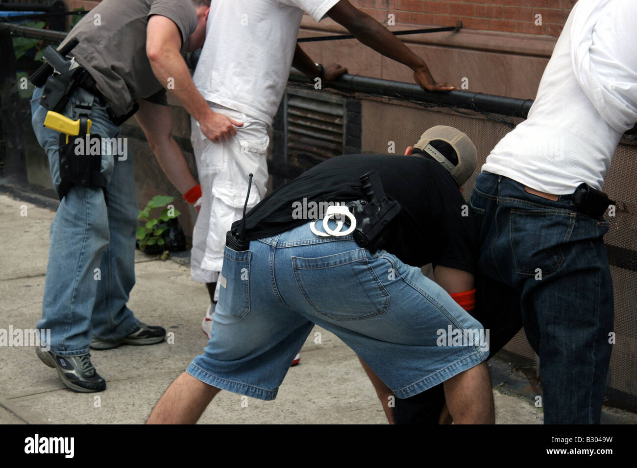 Plain clothes detectives searching suspects in Harlem New York City - Stock Image