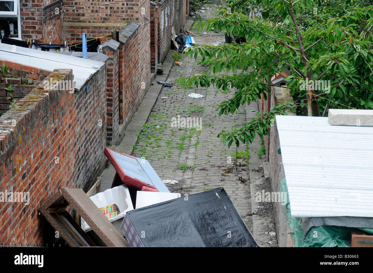 Urban mess, rubbish dumped in a terrace back ally, Manchester, Northern England - Stock Image