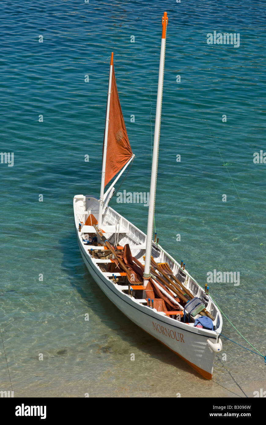 Pilot gig 'Nornour' ashore on St Agnes, Isles of Scilly, Cornwall, UK.  The mast is an unusual addition - Stock Image