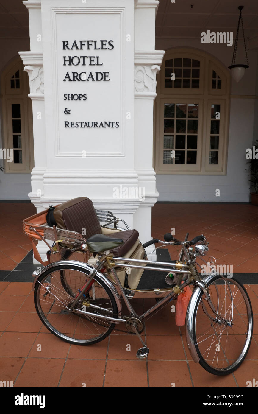 Trishaw outside historic Raffles Hotel, Singapore - Stock Image