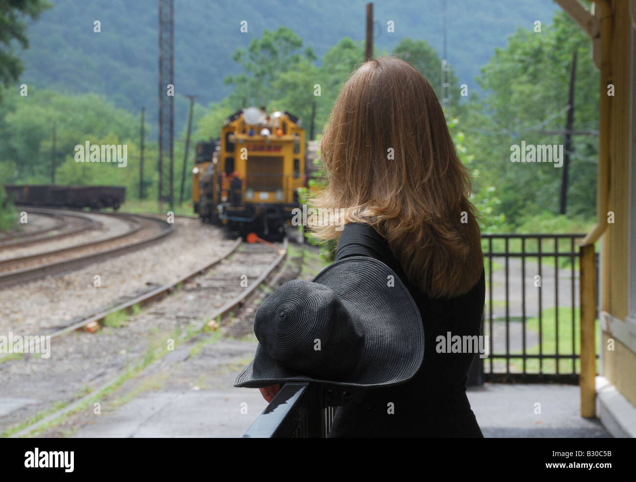 woman with black hat waits for train - Stock Image