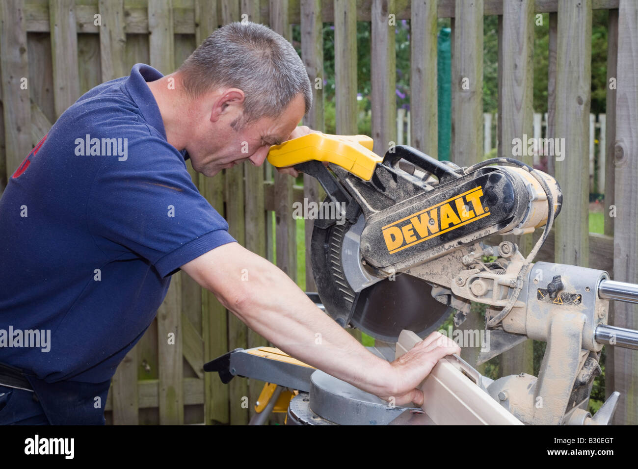 Man using a De Walt circular saw power tool to cut a piece of wood outside. UK Britain - Stock Image