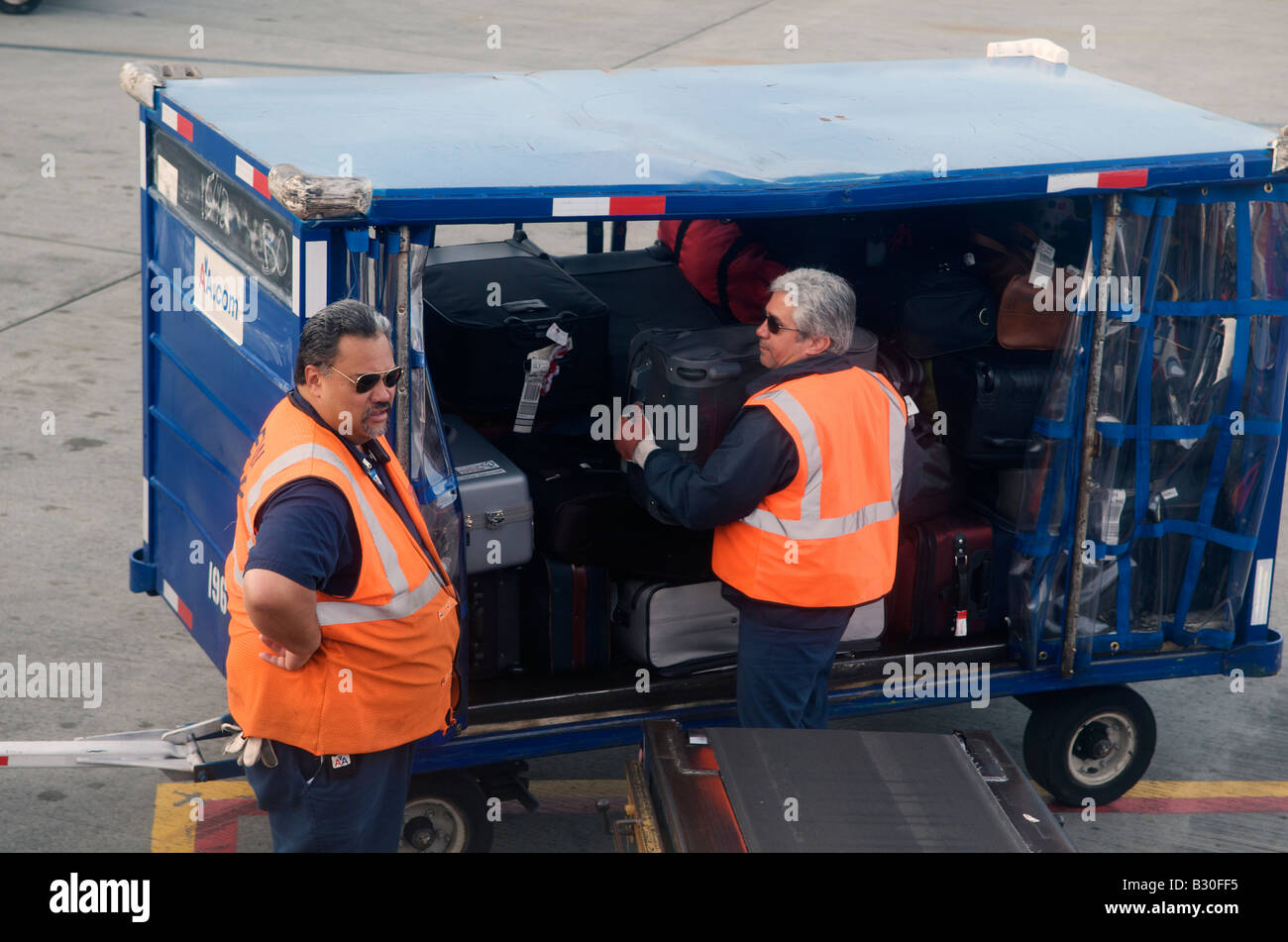 baggage handlers load suitcases on to a conveyer belt at Dallas Fort Worth International Airport in Texas, United - Stock Image