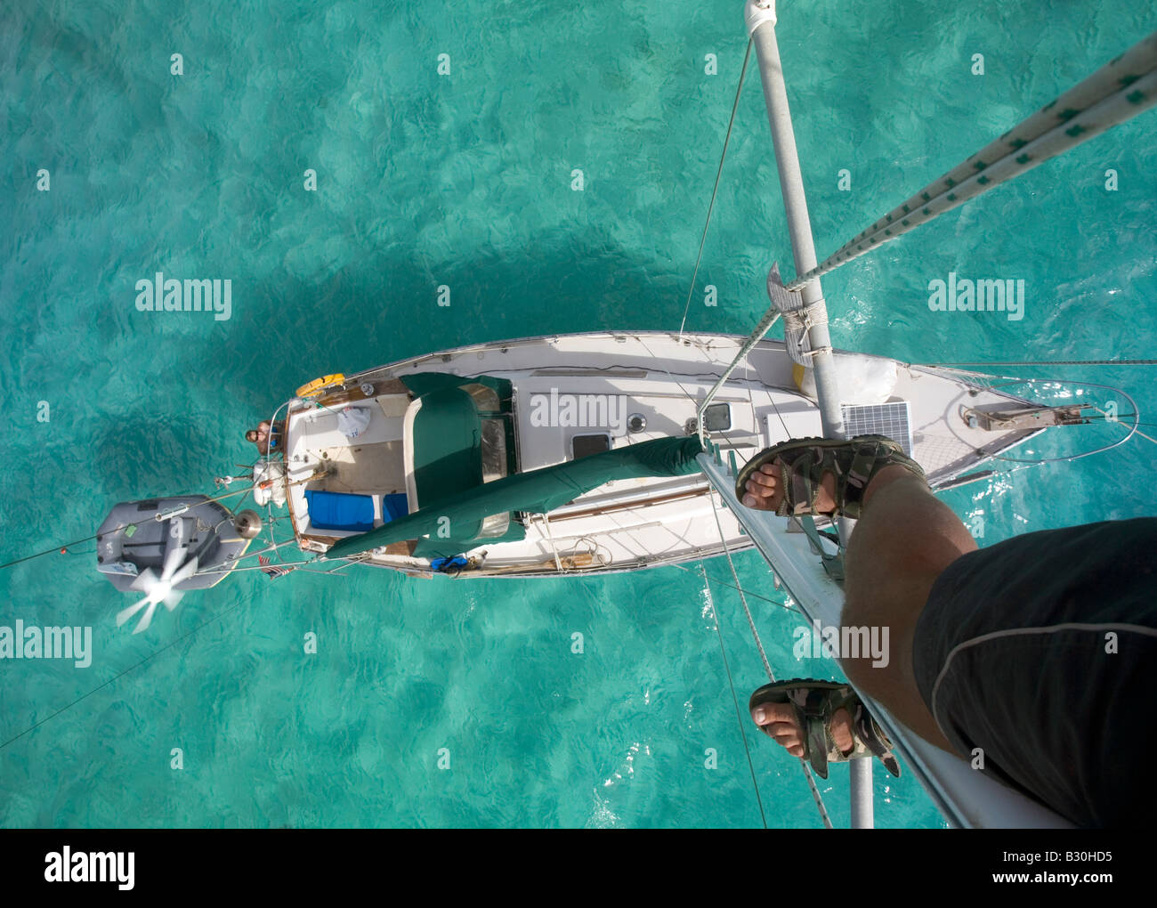 Looking down at a cruising sailboat in the Caribbean The boat sports a wind generator and a solar panel and mast - Stock Image