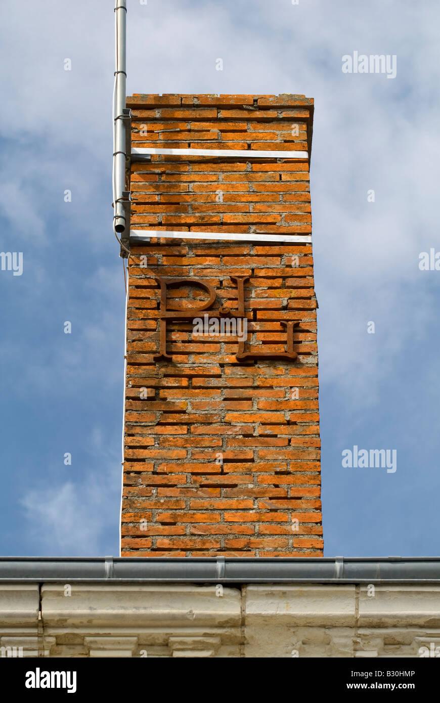 Decorative letters 'PL' reinforcing chimney stack, France. - Stock Image