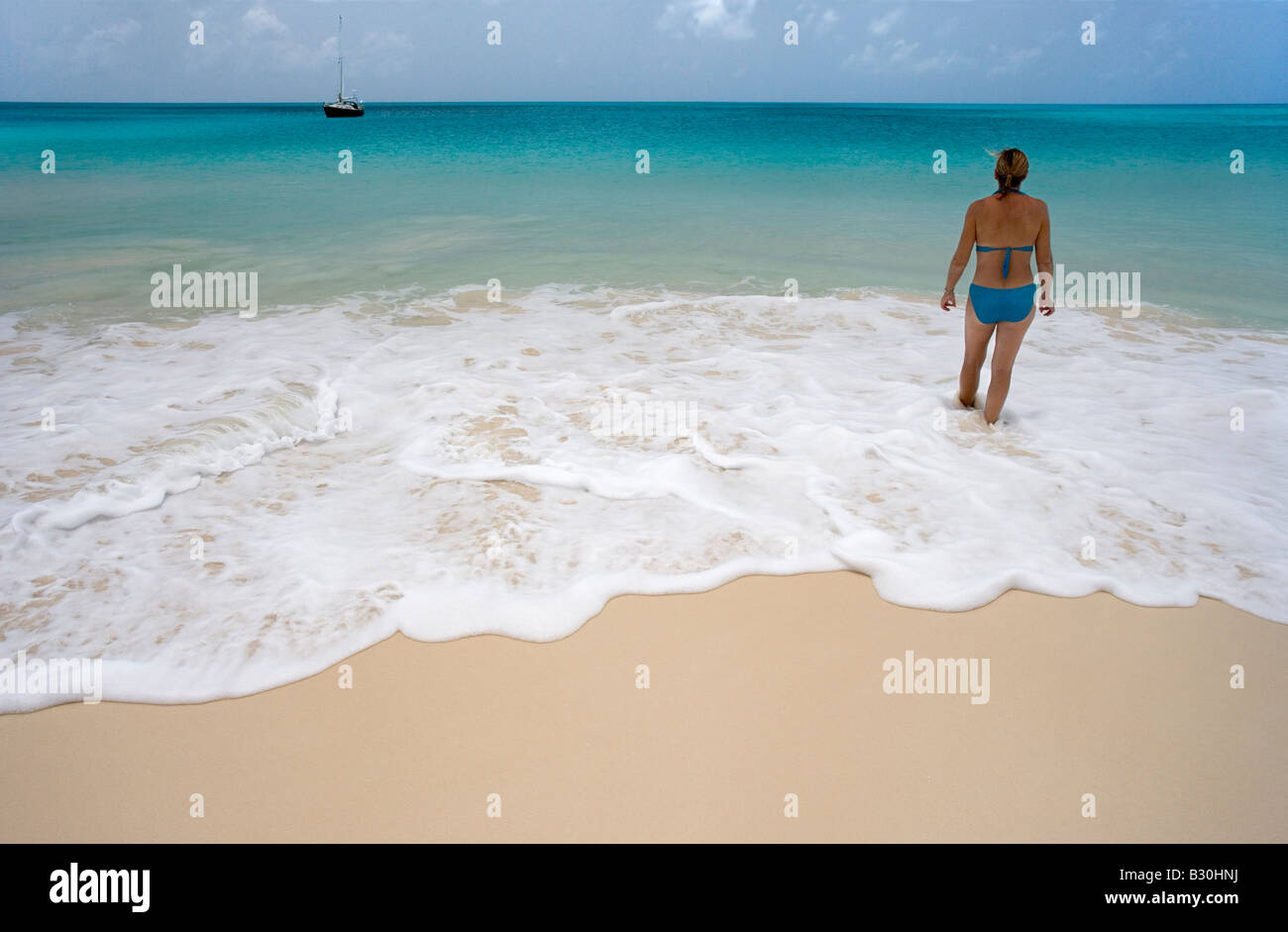 A woman wades in the gentle surf of 11 Mile Beach on Barbuda s west coast Her sailboat swings to its anchor just - Stock Image