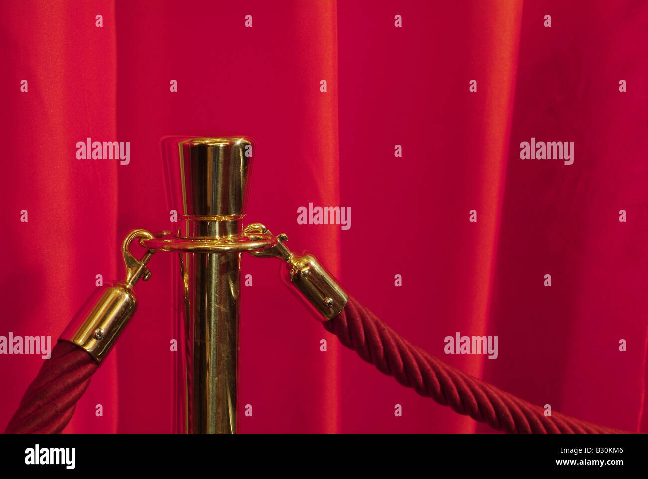 Red cords on a gilded pole - Stock Image