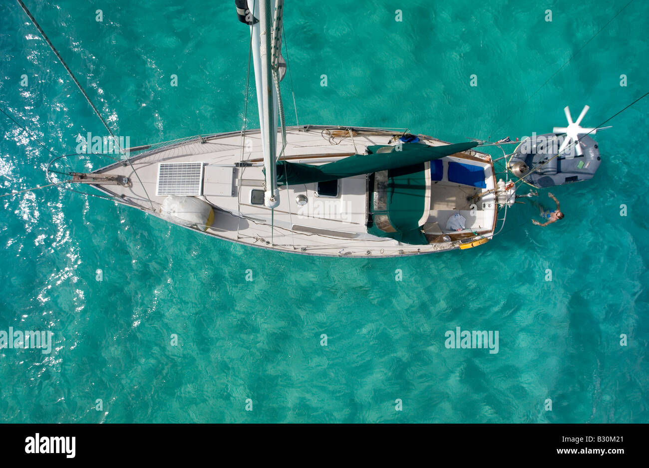 Looking down at a cruising sailboat in the Caribbean The first mate is having a swim - Stock Image