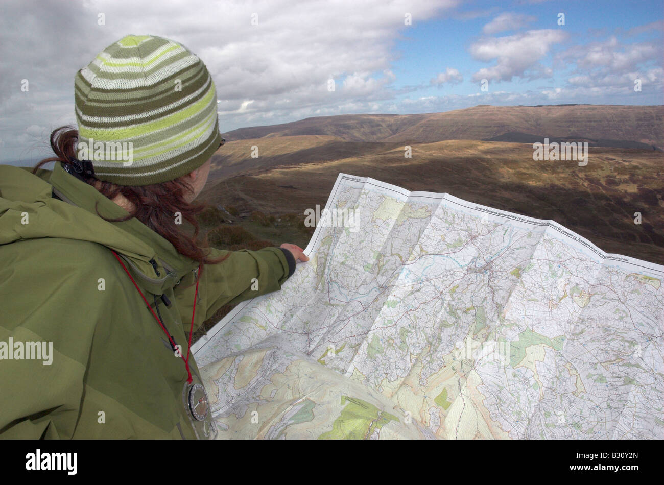 A walker looking at a map in the Brecon Beacons - Stock Image