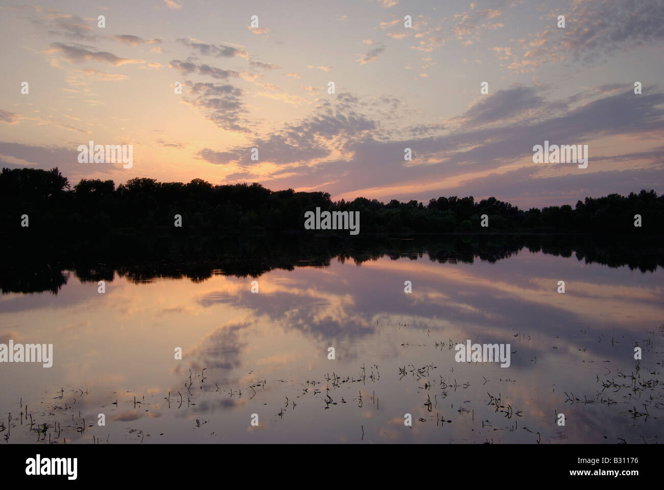 sunset reflected on a lake - Stock Image