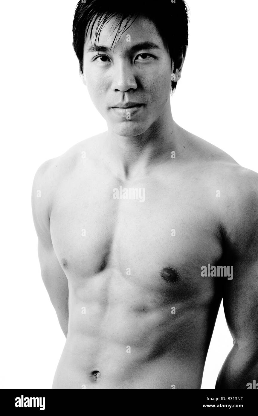 A muscular chinese male model on white background (monochrome) - Stock Image