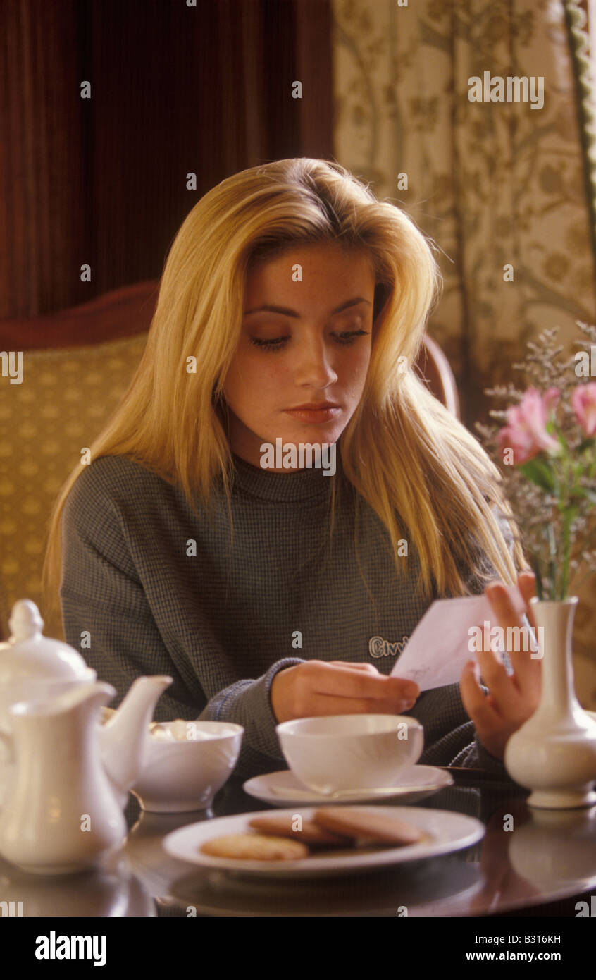 woman reading bill for coffee and biscuits - Stock Image