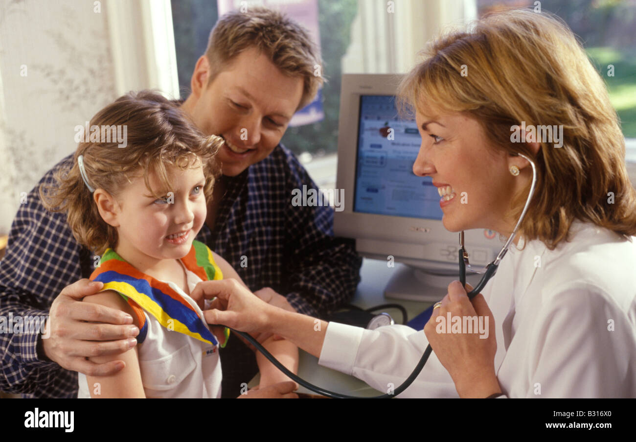 little girl with her father with doctor listening to her chest Stock Photo
