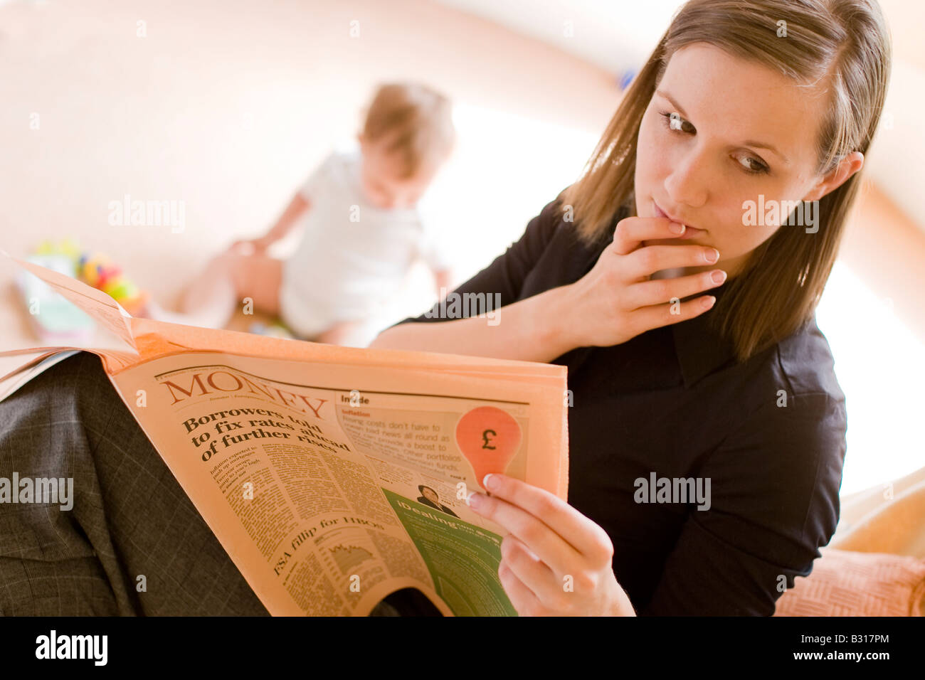 mother looking at worrying financial news in the paper with baby in the background - Stock Image