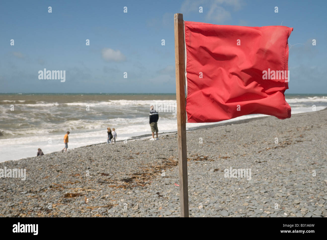 Red danger flag on beach warning of perilous swimming conditions Aberystwyth beach Wales UK - Stock Image