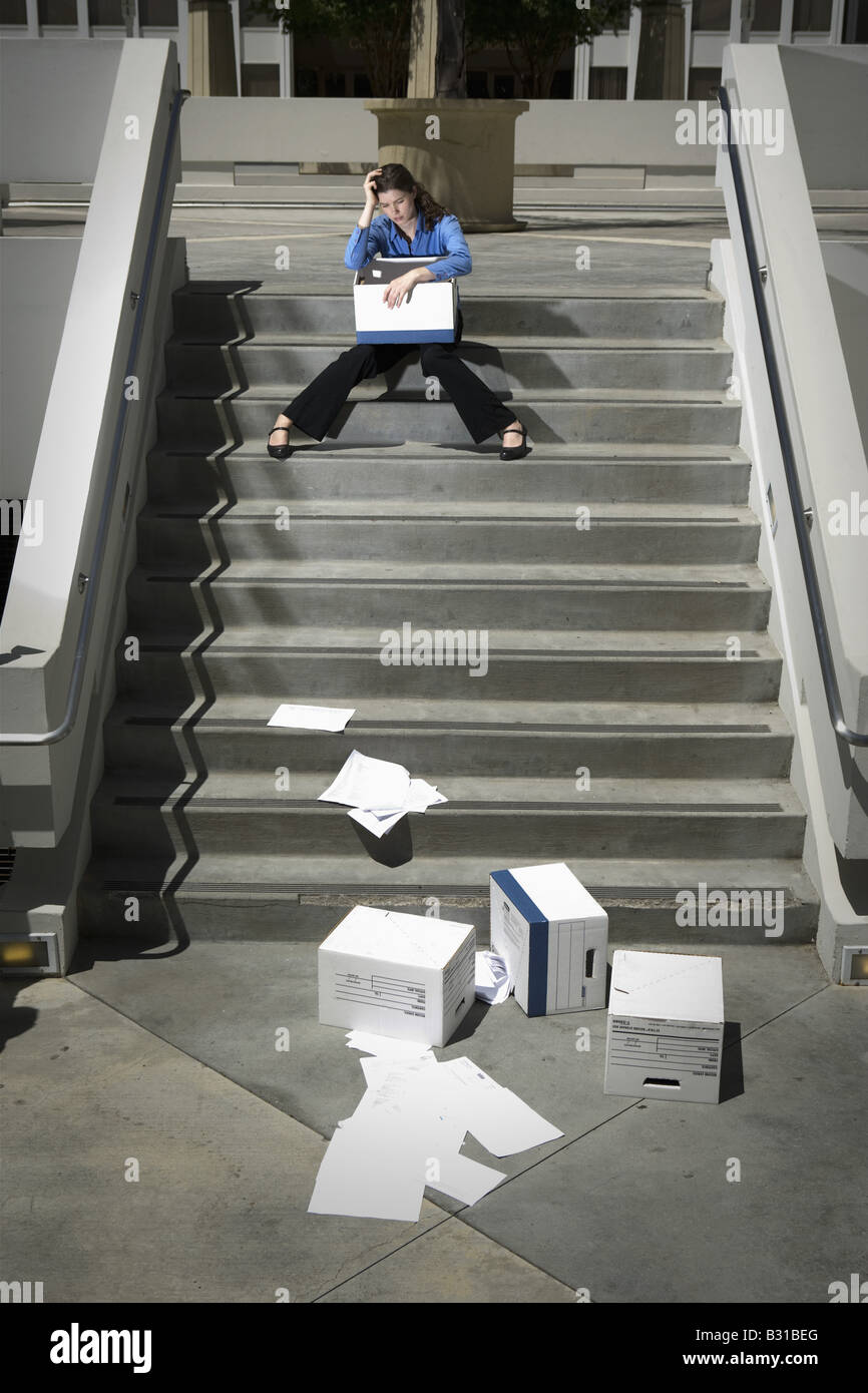 Girl Friday sitting on steps by dropped boxes of paperwork - Stock Image